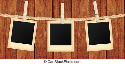 old photo cards hanging on rope on clothespins over wooden...