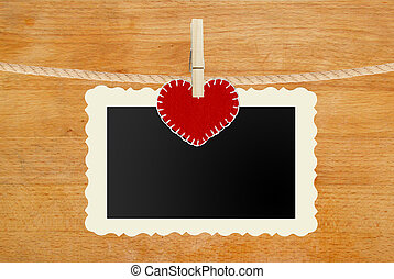 photo paper and red heart hanging on rope on wooden...