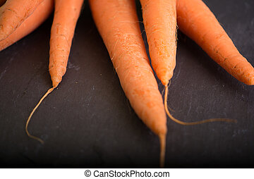 Carrots on a black background - Ripe fresh carrots with...