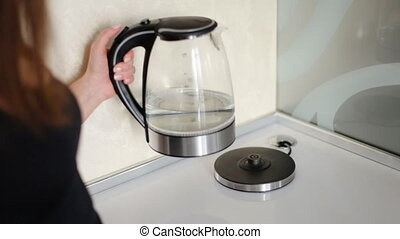Beautiful woman turning on modern glass electric kettle on...