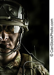 military man in camouflage wearing helmet, glasses, radio...