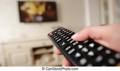 Hand holding TV remote control and changing channels on...