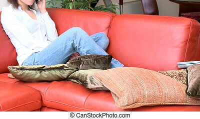 Jolly woman talking on phone sitting on sofa at home