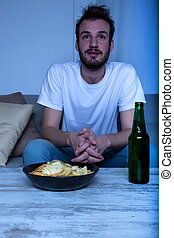 Young man watching a movie at nighttime with chips and beer...