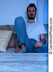 A young man bored in front of the TV at night - A young...
