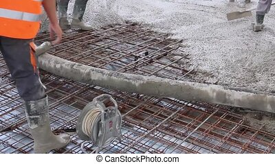Workers are spreading concrete over - Construction workers...
