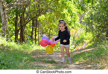 Little girl playing in autumn park