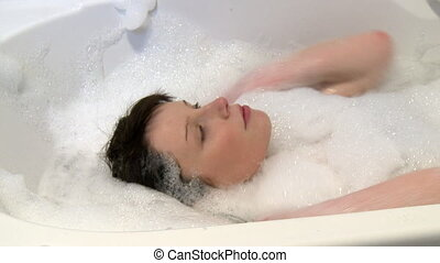 Beautiful woman having a bath at home