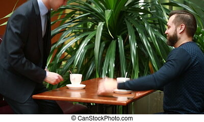 Two businessmen shaking hands in a cafe discuss business and...