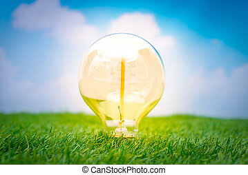 Eco concept - light bulb grow in the grass against blue sky