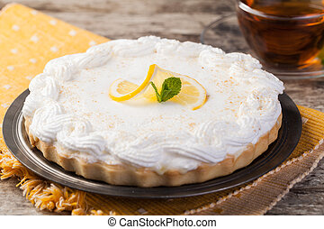 lemon tart on a plate decorated with lemons