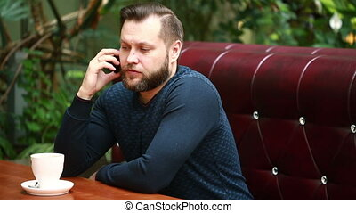 Handsome bearded businessman talking on the phone cheerfully...