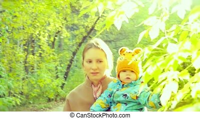 Happy mother and baby son resting in the autumn forest in...