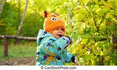 Toddler boy walking in the park at the autumn day Doing his...