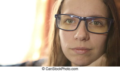young woman in glasses looking at the camera HD