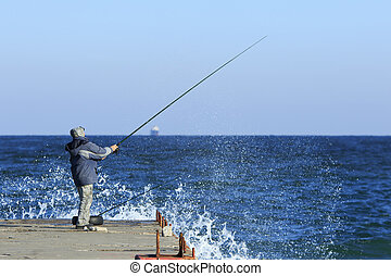 Fishing in stormy weather - Fishman stands on a pier holding...