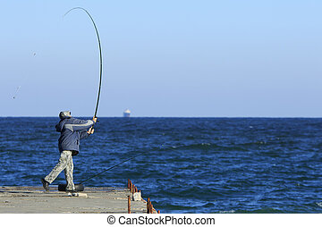 Fisher makes a throw - fiherman stands on the pier and...