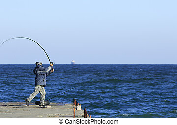 Fisher throws spinning - fisherman swings his spinning...
