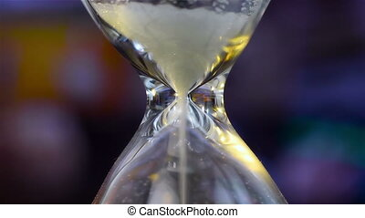 Sand Flowing Through An Hourglass. Close Up