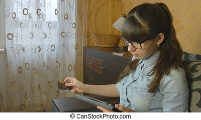 Beautiful woman shopping online with credit card and tablet at home