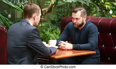 discussion in a coffee shop by two businessmen. sitting in...