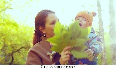 Mother has a fun with her Child in yellow autumn forest in slowmotion. 1920x1080