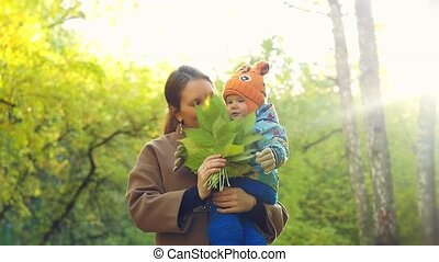 Mother has a fun with her Child in yellow autumn forest in...