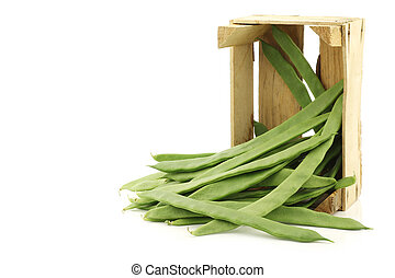 fresh string beans in a wooden crate on a white background