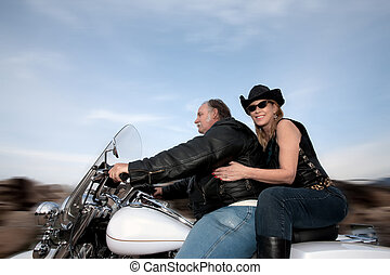 Motorcycle couple - Couple riding a motorcycle outside...