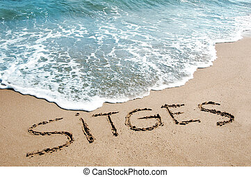 sitges written on the sand of a beach