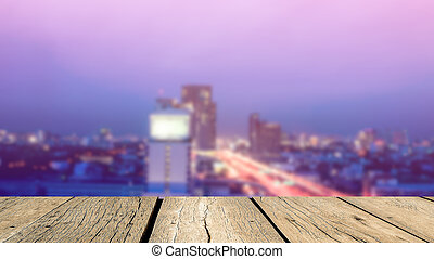 Wood floor in yellow brown color tone with blurred abstract background of Bangkok night lights downtown city view with bokeh in vintage style color tone: Wooden table with blur retro cityscape