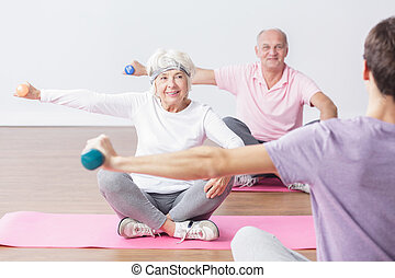 Sport is for everyone! - Seniors during exercises on gym...