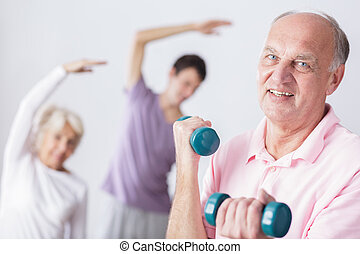 Gym is my second home - Senior man holding dumbbells and...