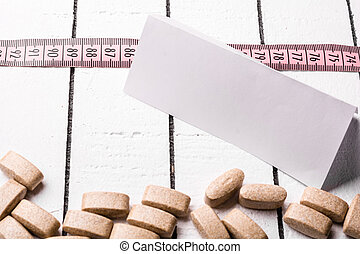 Pills, blank sheet of paper and pink measuring tape over the white wooden background