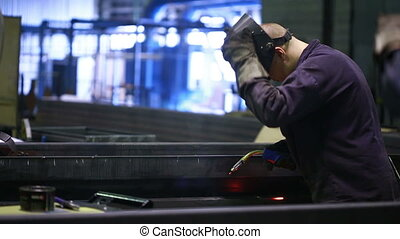Worker with protective mask welding metal factory