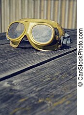 Filtered picture of a vintage safety glasses on a wooden...