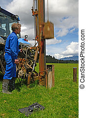 seismic testing - A man uses a fence post driver to generate...