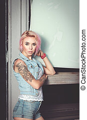 beautiful girl with a tattoo stands near the door