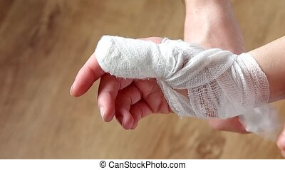 Hand bandaged with a bandage - Unwinding the bandage from...