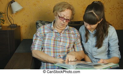 Old and young woman looking at family photo album on sofa at...