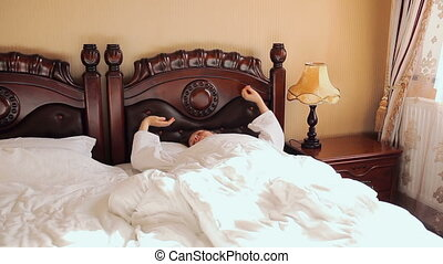 Young woman wake up in classic interior room and looking at...