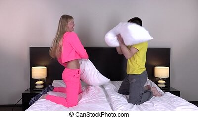 Happy couple having pillow fight on the bed, slowmotion -...