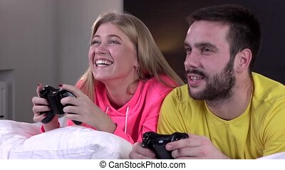 Young couple in pajamas playing video game together,...