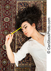 Young brunette student woman thinking with pencil