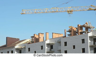 Construction crane working on a luxury object. Workers lay...