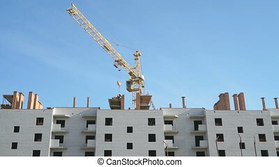 Construction crane working on a apartment building -...