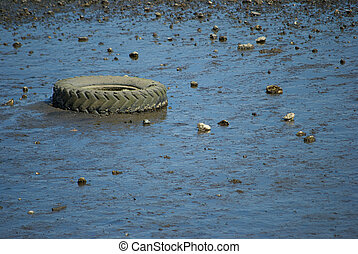 Tire on the Beach - An old tire stuck in the sand is exposed...