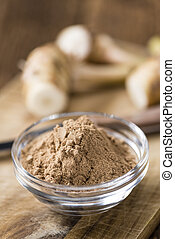 Galangal Powder(detailed close-up shot) on an old wooden...