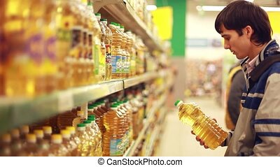 Man taking a bottle of oil from a shelf in a supermarket...