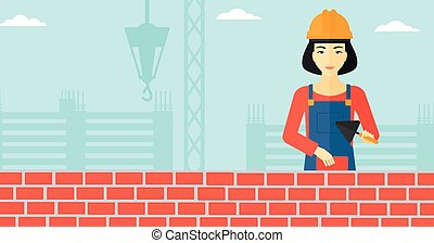 Bricklayer with spatula and brick - An asian female...